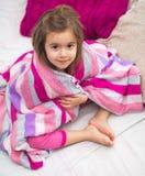Uma menina com uma cobertura na cama Fotografia de Stock Royalty Free