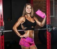 Uma menina com uma garrafa no gym imagens de stock