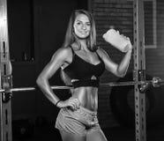 Uma menina com uma garrafa no gym imagem de stock royalty free