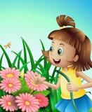 Uma menina com uma mangueira no jardim Imagens de Stock