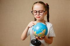 Uma menina com vidros está procurando um lugar no globo imagem de stock