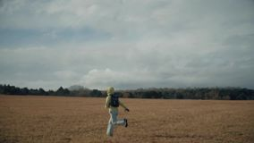 Uma menina corre através do campo video estoque