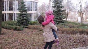 Uma menina corre para a mamã Os abraços da mãe, círculos, beijam a criança video estoque