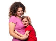 Uma menina cortada ao abraçar sua mamã firmemente fotos de stock