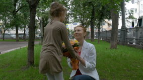 Uma menina dá a sua mãe um ramalhete das flores vídeos de arquivo