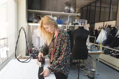 Uma menina da costureira está estando em um estúdio perto de uma tábua de passar a ferro e de uma roupa passando workplace imagem de stock royalty free