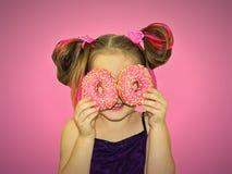Uma menina da criança chapinha e joga com os dois anéis de espuma frescos antes de comer Uma criança guarda anéis de espuma perto imagens de stock royalty free