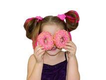 Uma menina da criança chapinha e joga com os dois anéis de espuma frescos antes de comer Uma criança guarda anéis de espuma perto foto de stock royalty free