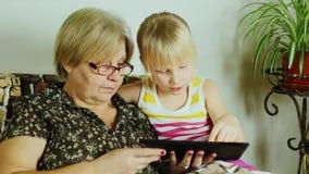 Uma menina da criança de 6 anos com uma avó usou uma tabuleta junto filme
