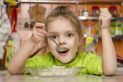 Uma menina da criança de quatro anos come com uma forquilha e uma colher que sentam-se na tabela na cozinha Foto de Stock Royalty Free