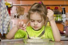 Uma menina da criança de quatro anos come com uma forquilha e uma colher que sentam-se na tabela na cozinha Foto de Stock
