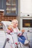 Uma menina da criança do ano senta-se na cadeira alta do bebê com a garrafa de alimentação em sua mão Foto de Stock