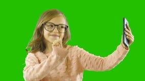 Uma menina da idade escolar que guarda um telefone olha nele e é surpreendida, virada com emoções pronunciadas, fundo isolado video estoque