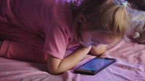 Uma menina da idade pré-escolar com cabelo louro, vestida em um t-shirt cor-de-rosa e nas calças da luz que reclinam em sua cama, filme