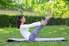 Uma menina da ioga que dá certo em um parque ensolarado Exercícios simples da manhã Prática de relaxamento dos asanas Menina saud Fotos de Stock