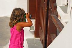 Uma menina das pessoas de 3-4 anos fotografa uma cerca de madeira em Imerovigli imagem de stock