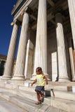 Uma menina das pessoas de 3-4 anos perto da universidade de Atenas fotografia de stock