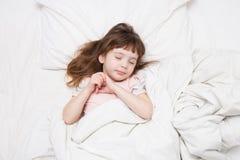 Uma menina de 4 anos que dorme na cama branca Imagens de Stock