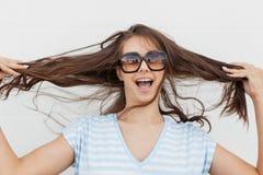 Uma menina de cabelo escuro magro bonito nova, roupa ocasional vestindo, está olhando a câmera e está guardando seu cabelo fotografia de stock