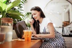 Uma menina de cabelo escuro de sorriso bonita, vestida no estilo ocasional, trabalha duramente em uma cafetaria moderna Facial fo imagem de stock