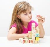 Uma menina de dúvida que joga com cubos de madeira Foto de Stock Royalty Free