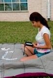 Uma menina de faculdade que joga o dominó Fotografia de Stock