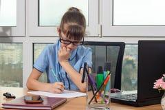Uma menina de oito anos na tabela no escritório escreve pensativamente uma pena em uma folha de papel imagens de stock royalty free