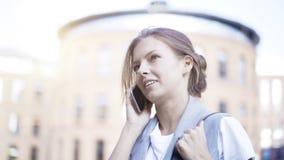 Uma menina de pensamento ocupada nova está tendo uma chamada fora fora Imagens de Stock Royalty Free