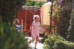 Uma menina de sete anos encantador alegre aprecia uma manhã ensolarada do verão e tem o divertimento no jardim em casa fotografia de stock