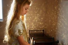 Uma menina de sete anos vestida em um vestido esperto decorado com sparkles do ouro está estando na sala, a luz solar imagens de stock royalty free
