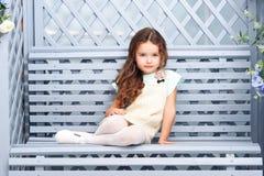 Uma menina de sete com cabelo da castanha senta-se em um banco de madeira em uma cor cinzento-azul, sorrindo com roupa e as ondas Fotos de Stock