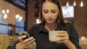 Uma menina de sorriso bonita que senta-se no café usando o smartphone e bebendo o café vídeos de arquivo