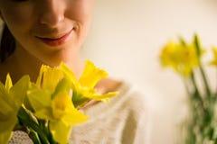 Uma menina de sorriso com um ramalhete da mola amarela floresce, narciso Fotos de Stock Royalty Free