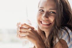 Uma menina de sorriso fina bonita nova com cabelo longo, estilo ocasional vestindo, está olhando a câmera e está guardando um vid foto de stock royalty free