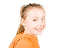 Uma menina de sorriso na laranja Imagens de Stock