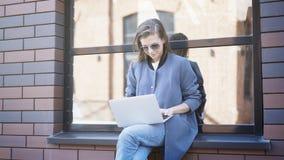 Uma menina de sorriso nova nos óculos de sol está sentando-se em um peitoril que datilografa em um portátil foto de stock royalty free