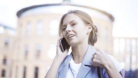 Uma menina de sorriso ocupada nova está tendo uma chamada fora fora Foto de Stock