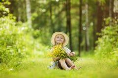 Uma menina de sorriso pequena bonito no campo dos girassóis que guardam um grupo de flores enorme em umas horas de verão ensolara Foto de Stock Royalty Free