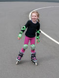 Uma menina de sorriso pequena que pratica inline (rolo) patinar no estádio exterior foto de stock royalty free