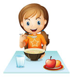Uma menina de sorriso que come seu café da manhã Fotografia de Stock Royalty Free