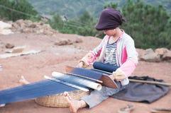 Uma menina de tecelagem imagem de stock