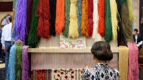 Uma menina de Usbequistão tece a cobertura Imagens de Stock