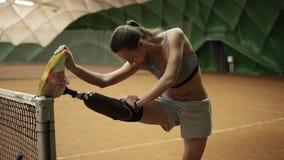 Uma menina deficiente delgada estica seu pé ferido na rede do tênis antes do jogo prosthesis dentro vídeos de arquivo