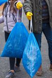 Uma menina do adolescente com um paizinho, está guardando sacos de lixo completos nas mãos Close-up fora fotografia de stock