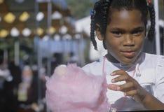 Uma menina do African-American que come doces de algodão, imagem de stock royalty free