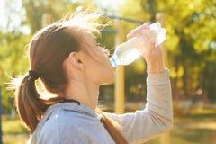 Uma menina do atleta bebe a agua potável após a formação Boca seca, restauração da energia vital fotos de stock royalty free