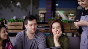 Uma menina do garçom que vista um avental aceita uma ordem de três amigos com cabelo escuro que se senta em um restaurante e esco filme