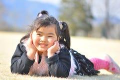Uma menina do Malay sorri no campo de A durante a mola Imagens de Stock