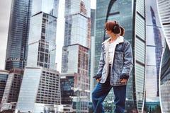 Uma menina do moderno com tatuagem em sua cara na moda vestiu fones de ouvido vestindo que escuta a música na frente dos arranha- fotos de stock