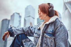 Uma menina do moderno com tatuagem em sua cara na moda vestiu fones de ouvido vestindo que escuta a música na frente dos arranha- fotografia de stock royalty free